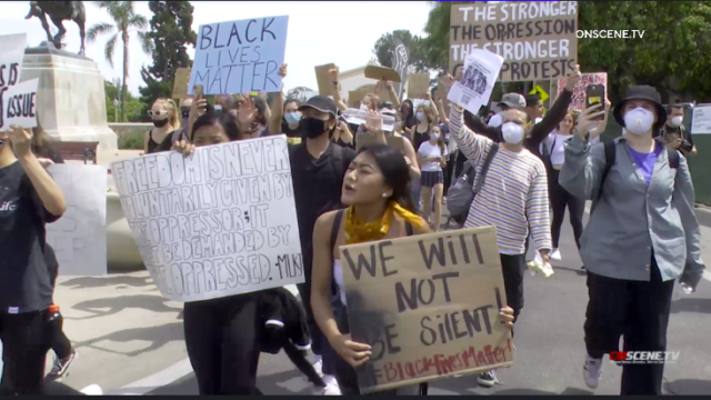 Protesters march in Balboa Park after being allowed into closed park.