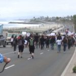Protesters march along the coast in Carlsbad