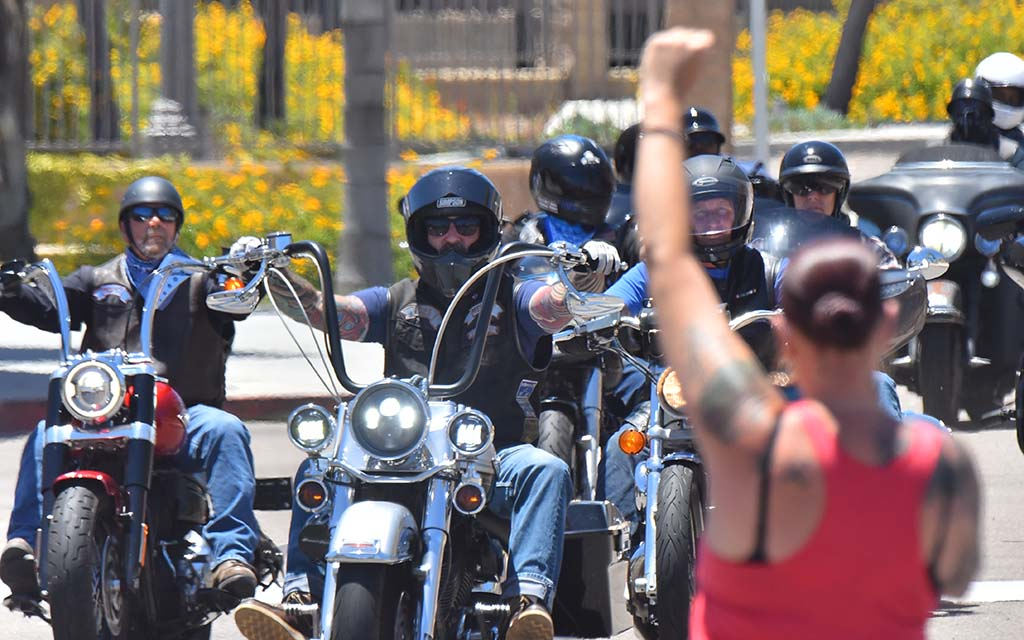 A protester raises her fist to members of motorcycle groups that supported the protest at the La Mesa Police Department parking lot on June 14.