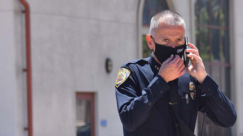 La Mesa Police Chief Walt Vasquez takes a call as he stands outside the La Mesa Police Department building.