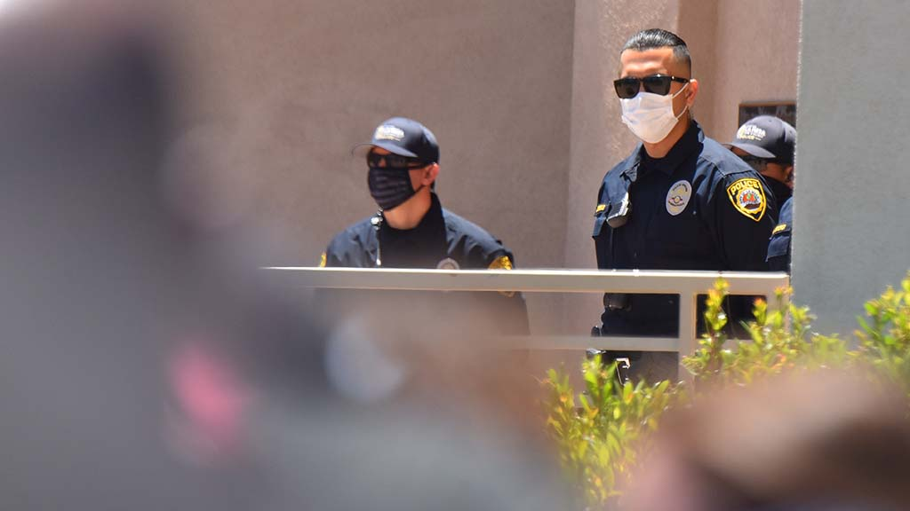 Members of the La Mesa Police Department view protesters from outside the building's front door.