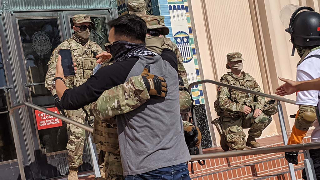 A protester and a National Guard member hug on the steps of the San Diego County Administration during a second protest there on June 6.