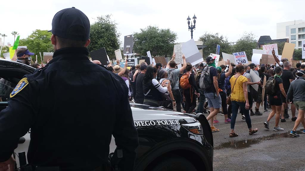 Protesters walk past police cars that were parked along Ash Street at the beginning of the route.