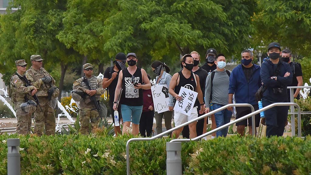 Protestors walk past National Guard troops guarding the San Diego County Administration building on June 6.