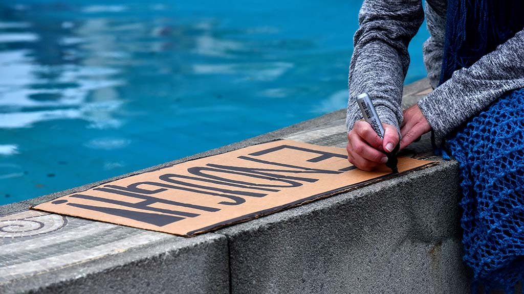 A protester prepared a sign before the beginning of a Black Lives Matter protest by the San Diego County Administration Building.