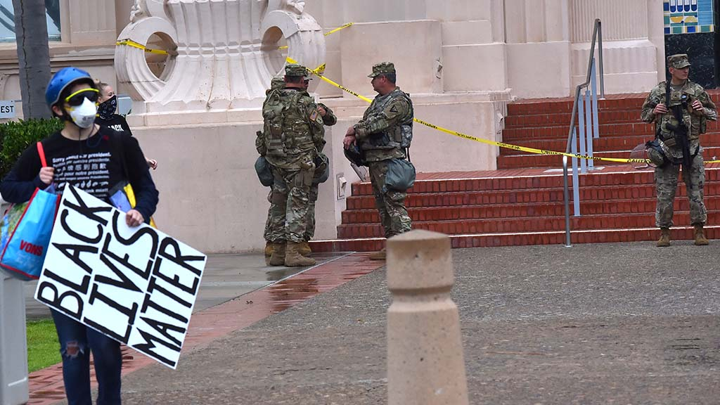 National Guard troops are stationed at the San Diego County Administration building as protesters arrive for a march.
