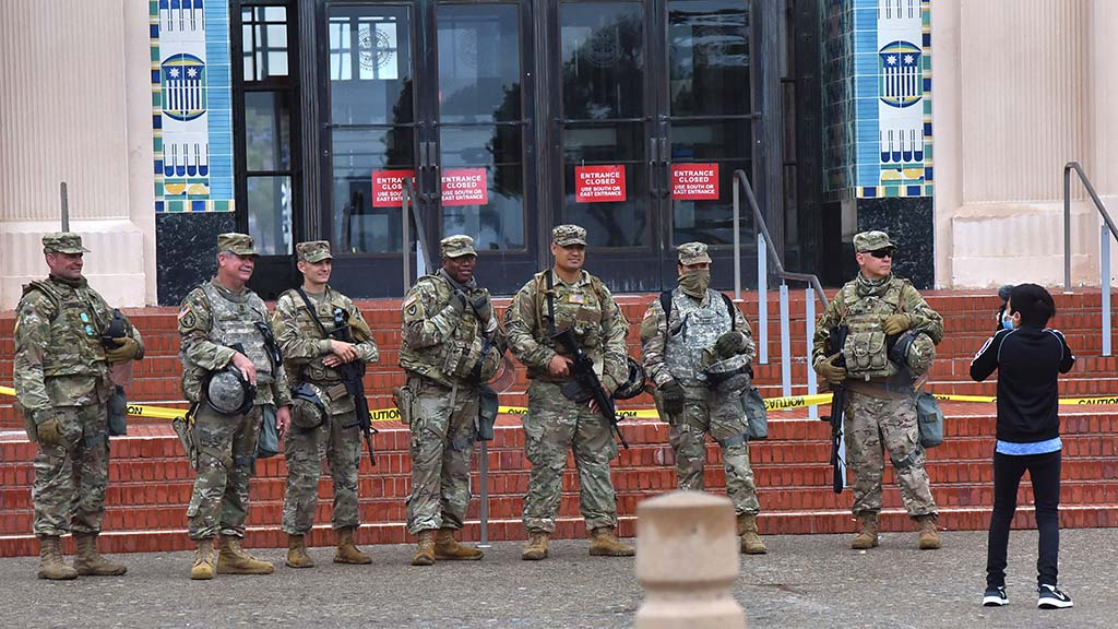National Guard troops pose for a photo for a young boy who accompanied family members to a protest and march.
