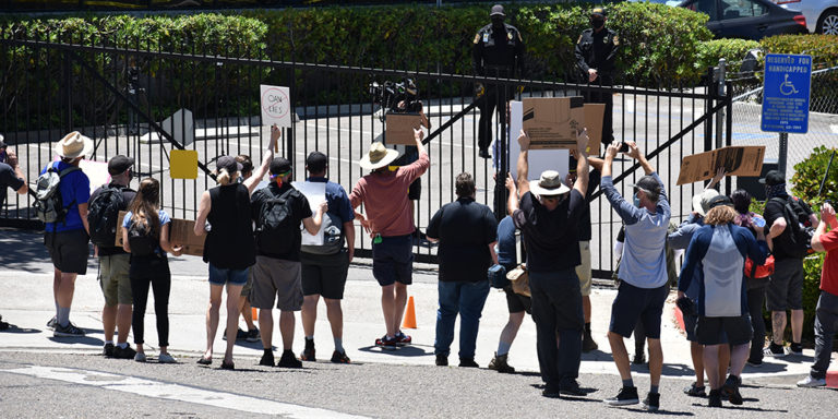 About 30 protesters demonstrate outside gate of One America News Network in Bay Ho area of San Diego.
