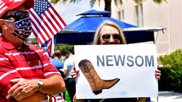 A simple sign made the point. Woman wants Gavin Newsom to get the boot.