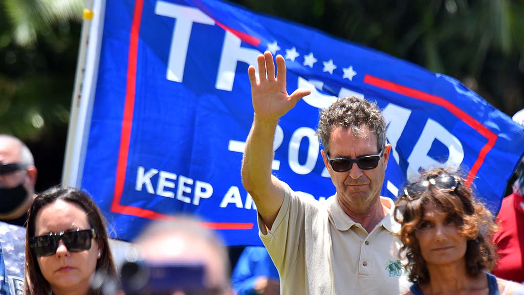 A rally-goer raise his hand during opening prayer by Pastor Leo Giovinetti of Mission Valley Christian Fellowship.