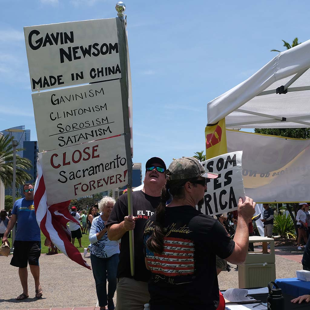 "Gavin Newsom was depicted by one sign as ""made in China"" at recall rally in downtown San Diego."