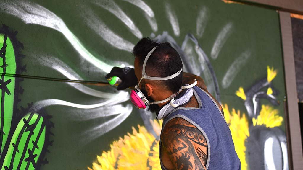 Artist Lourans Mikhail paints a mural with a bee to help beautify the La Mesa Shopping Center after business were looted and windows were smashed.