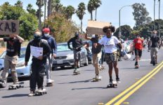About 100 Black, White and Latino young people carry signs as they ride north on Mission Bay Boulevard.
