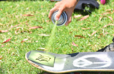 Protesters prepare for a Black Lives Matter demonstration by spray painting letters and symbols on their skateboards at Mission Bay Park.