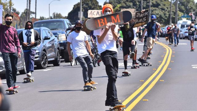 On skateboards, skates, scooters and bikes at San Diego Mission Bay Park, protesters demonstrate for racial equality.