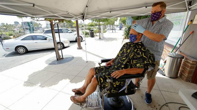 A barber in Solana Beach cuts hair on the sidewalk