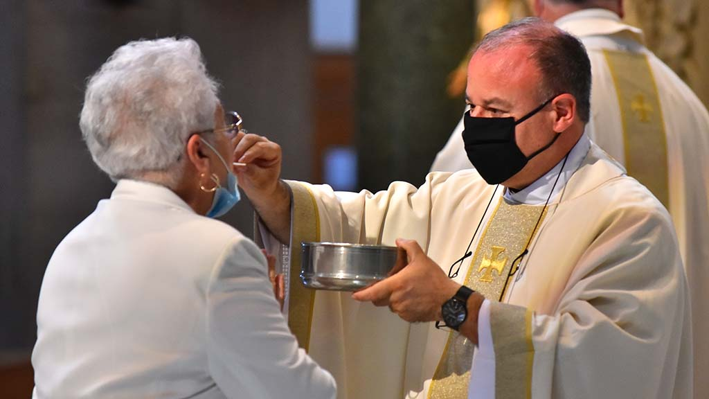New auxiliary bishop of San Diego, Ramón Bejarano, gives communion to his mother during his ordination ceremony at USD.