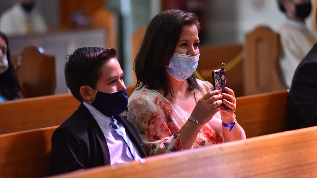 An attendee and her son watch as Ramón Bejarano is ordained bishop in the Immaculata at USD.