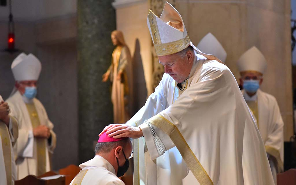 San Diego Bishop Robert McElroy places his hands on the head of Ramon Bejerano, who was ordained as an auxiliary bishop for the local diocese at the University of San Diego.