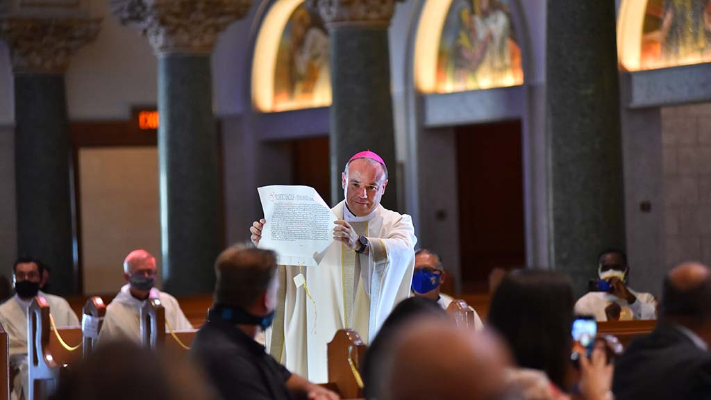 During an ordination ceremony, the Rev. Ramón Bejarano displays a letter from Pope Francis naming him a new bishop in San Diego.