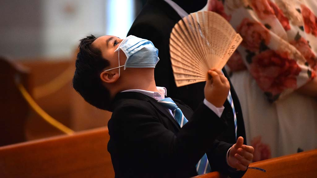 A young child fans him during an ordination ceremony amid warm weather in the University of San Diego's Immaculata Church.