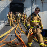Firefighters leaving the USS Bonhomme Richard