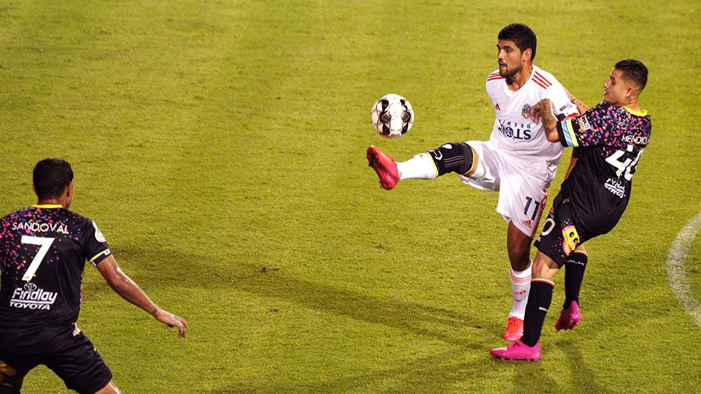 Loyal player Irvin Parra (center) advances the ball despite an opposing player's move.