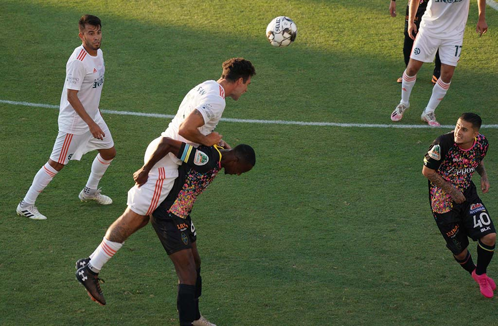 Loyal player Joe Greenspan leaps over a Las Vegas Lights player to do a header in the match at Torero Stadium