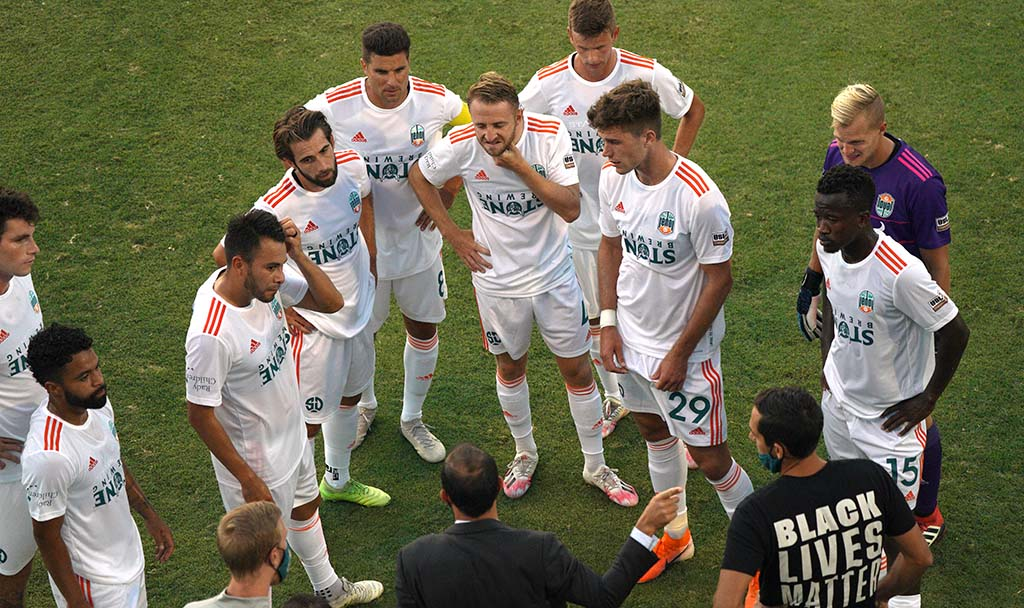 Loyal coach Landon Donovan (center bottom) talks strategy during a water break in the match at the University of San Diego.