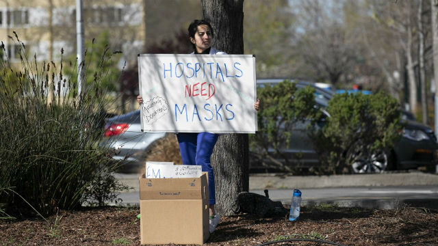 A medical student holds a sign asking for mask donations