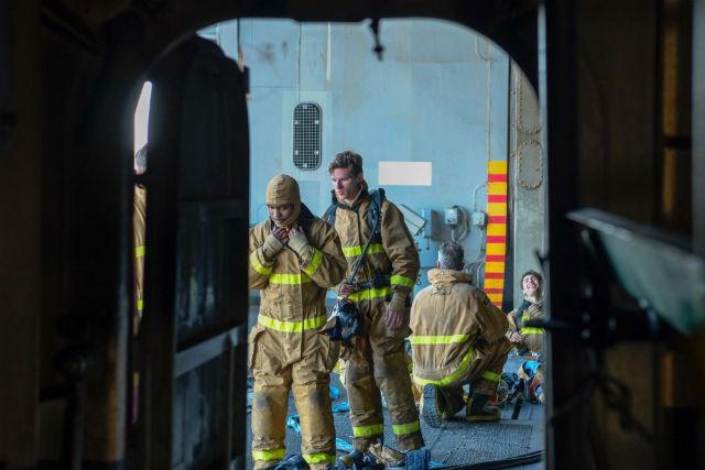 Exhausted firefighters aboard USS Bonhomme Richard