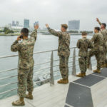 Marines wave as they leave San Diego