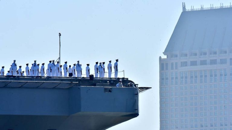 The Manchester Hyatt looms in the background as the USS Theodore Roosevelt returns to North Island Naval Air Station.