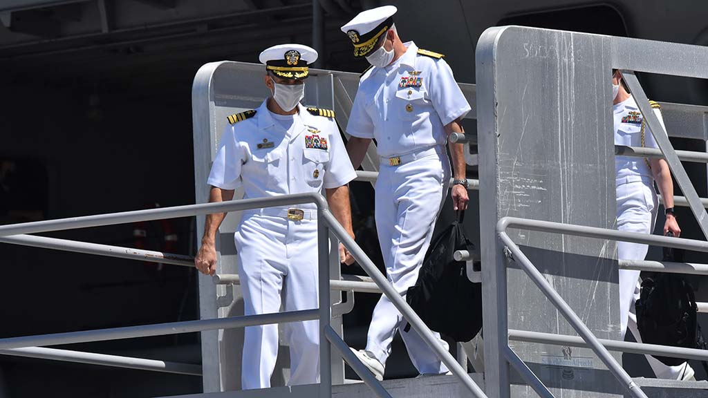 Rear Adm. Doug Verissimo, commander Carrier Strike Group 9,(center) and Capt. Carlos Sardiello depart the USS Theodore Roosevelt.