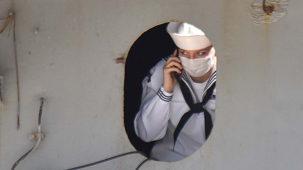 A sailor finds a place for cell phone reception while looking off the ship after the docking of the USS Theodore Roosevelt.