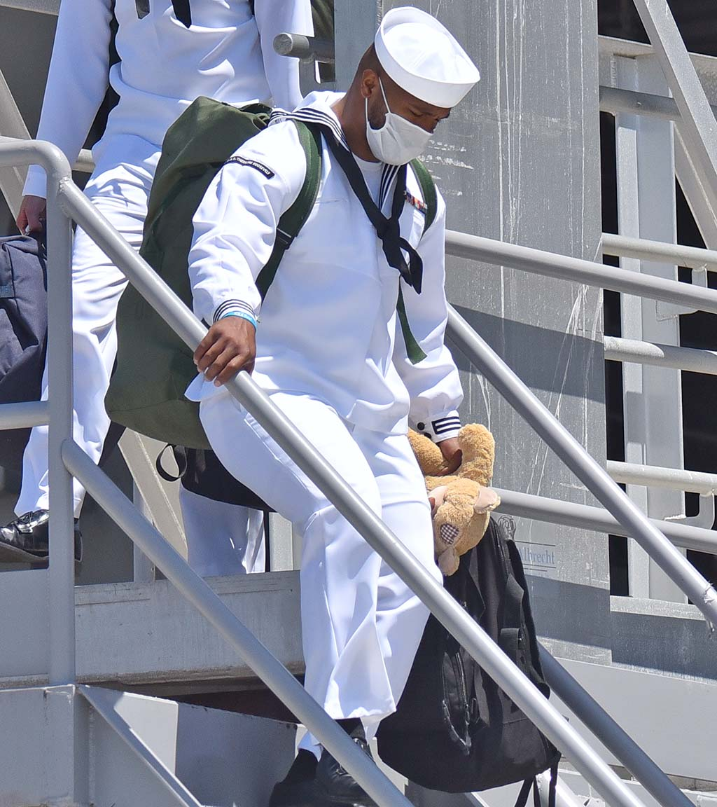A sailor departs the USS Theodore Roosevelt with a teddy bear gift.