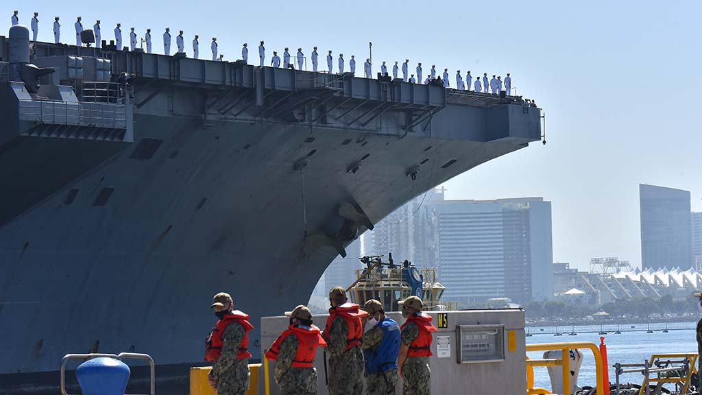 Sailors at Naval Air Station North Island wait to tie up the USS Theodore Roosevelt as it returned to port.