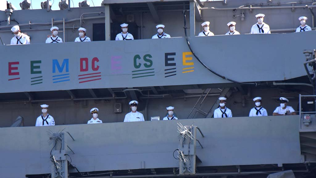 More than 5,000 crew members wearing masks aboard the USS Theodore Roosevelt wait for the ship to touch port after a tumultuous six-month deployment.