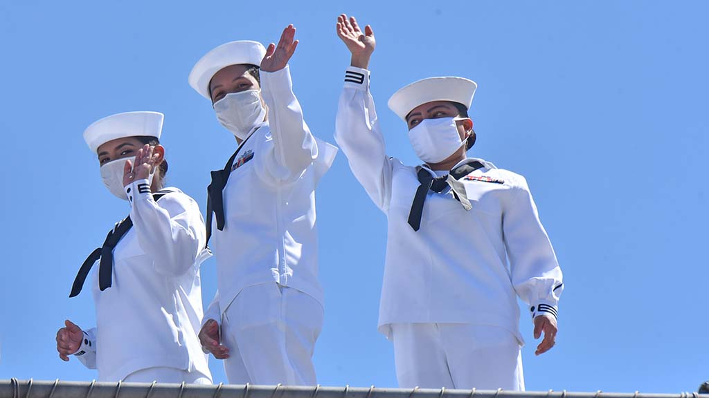 Sailors wave from the flight deck of the USS Theodore Roosevelt as it docked back home at Naval Air Station North Island.
