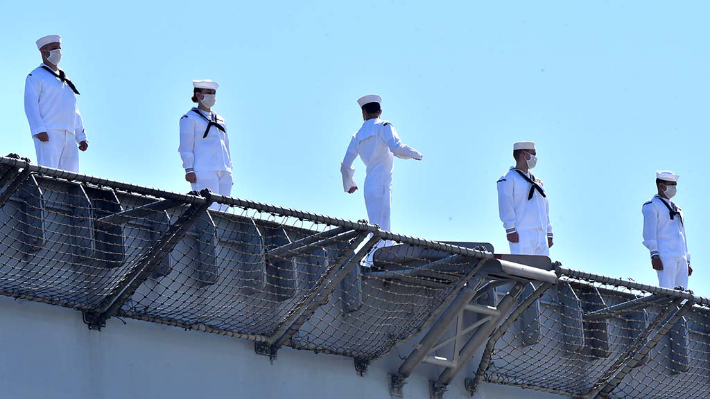 A sailor stretches as crew members were told to take a break while waiting to leave the USS Theodore Roosevelt.