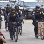 The last marcher holds up a sign as San Diego police officers follow June march on bikes.