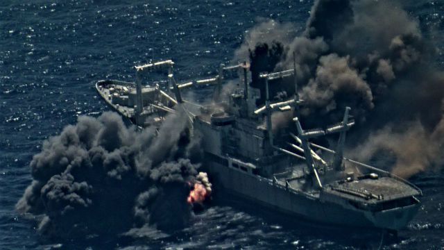 Flames and smoke pour from the former USS Durham