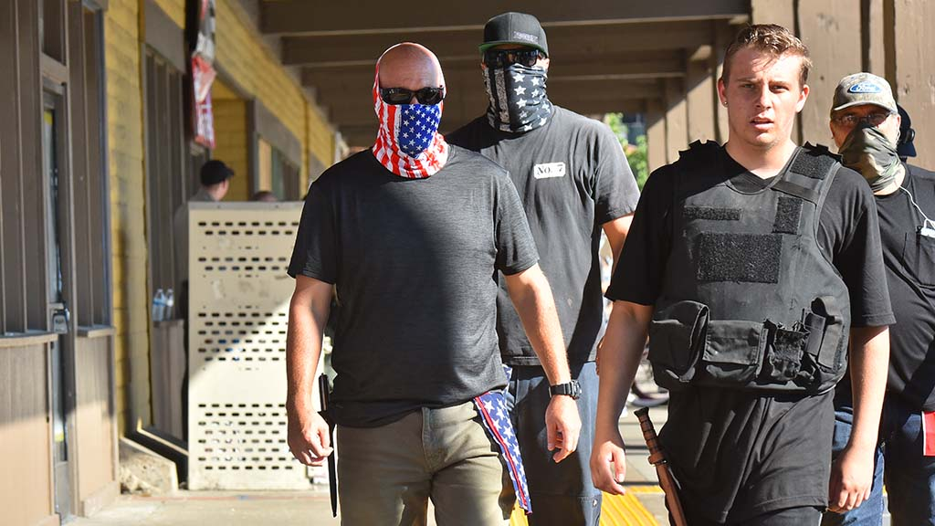 Counter protesters , some with knives and a club, walk around La Mesa Springs Shopping Center.
