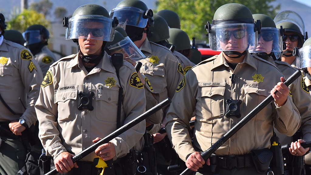 San Diego County Sheriff's deputies line up to follow the protesters' march