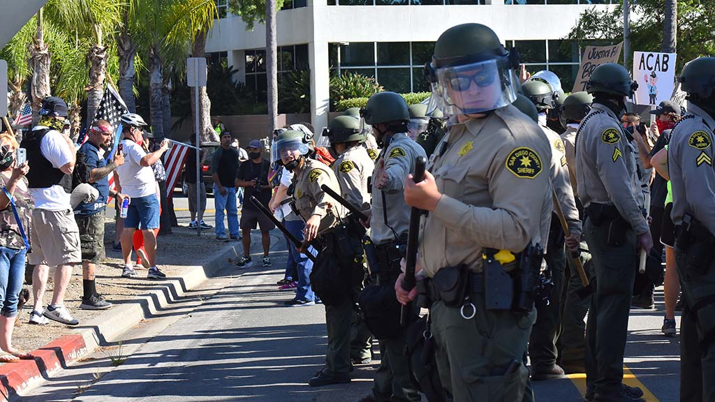 San Diego County Sheriff's deputies line up on Date Avenue to separate counter protesters from protesters near the Civics Center.