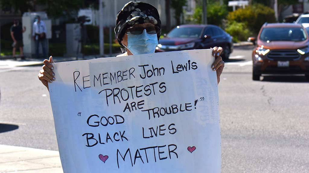 A woman shows up in La Mesa with her sign to support the BLM protest.