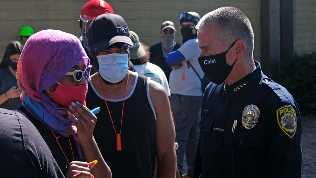 La Mesa Police Chief Walt Vasquez (right) speaks with protesters before a rally in La Mesa.