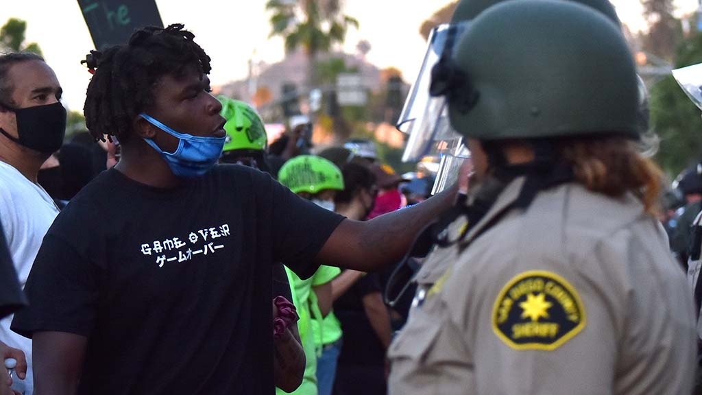 A protestor reaches out to sheriff's deputy at the end of a Black Lives Matter protest.