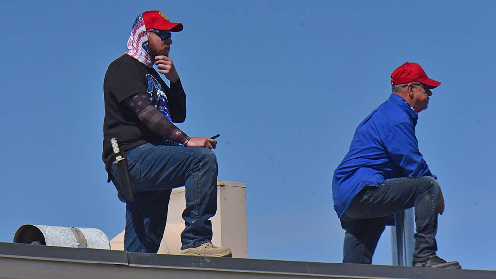 Members of a Facebook group called Defend East County watch from the roof of the Veterans of Foreign Wars building in La Mesa.