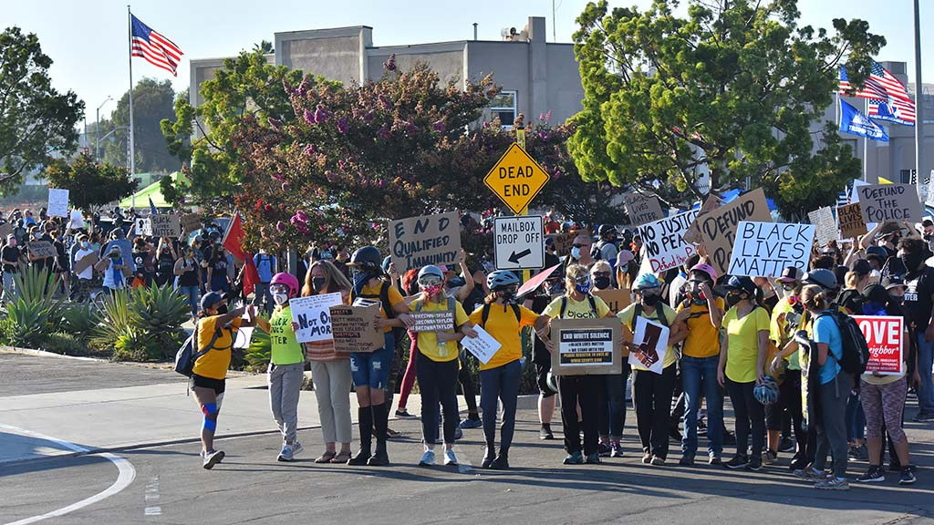 Demonstrators march into the La Mesa Police parking lot after protesting throughout La Mesa.